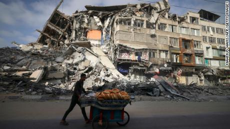 A Palestinian man walks past the destroyed Al-Shuruq building in Gaza City on Thursday.