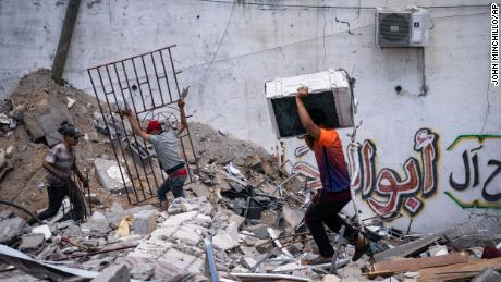 People reclaim materials from a building destroyed by Israeli airstrikes in Gaza City on May 22.
