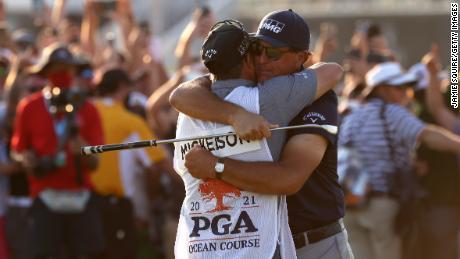 Микельсон празднует с братом и Кэдди Тимом Микельсоном на 18-м зеленом поле после победы на чемпионате PGA 2021 года.