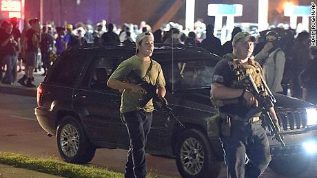 Kyle Rittenhouse, left, with backwards cap, in Kenosha, Wisconsin, with another armed civilian during chaotic protests in August 2020 over the police shooting of Jacob Blake, a Black man. Rittenhouse is accused of killing two people during the protests.