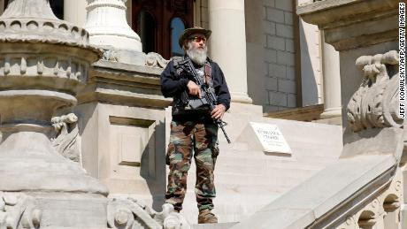 An armed demonstrator attends a rally in support of First Amendment rights  at the Michigan State Capitol in Lansing on May 15, 2021.