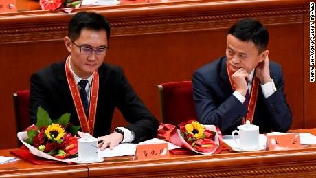 """Alibaba's co-founder Jack Ma (R) looks at Tencent Holdings' CEO Pony Ma during a celebration meeting marking the 40th anniversary of China's """"reform and opening up"""" policy at the Great Hall of the People in Beijing on December 18, 2018."""