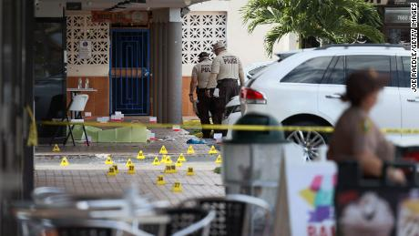 Miami-Dade police investigate Sunday near shell case markers on the ground.