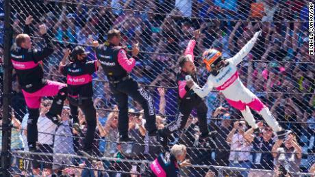 Helio Castroneves de Brasil celebra con su equipo mientras sube la valla en la línea de salida / meta después de ganar la carrera de autos 500 de Indianápolis en el Indianapolis Motor Speedway en Indianápolis, el domingo 30 de mayo de 2021.