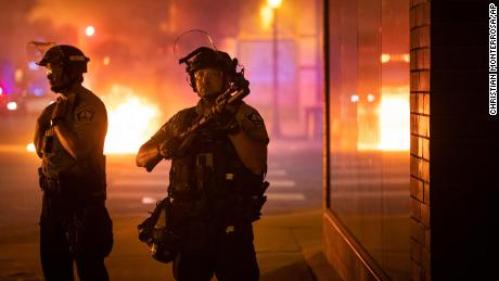 Police stand guard early Saturday after protesters set fire to trash bins in Minneapolis.
