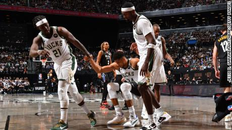 Jrue Holiday and Bobby Portis of the Bucks help up Antetokounmpo during their game against the Nets.