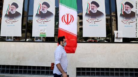Мужчина из Ирана просматривает плакаты Раиси перед офисом кампании в Тегеране 7 июня.