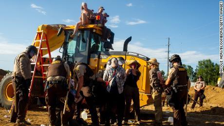 Demonstrators sit atop construction equipment as law enforcement officers detain other protesters Monday at an Enbridge Line 3 pump station.