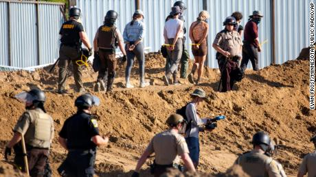 Activists are walked through an Enbridge Line 3 pump station Monday after being arrested.