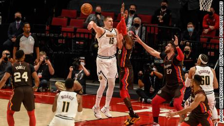 Jokic throws Monte Morris a no-look pass while Robert Covington defends of the Portland Trail Blazers.