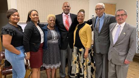 La familia de Pettyjohn posa con los funcionarios en la conferencia de prensa.  Incluían (de izquierda a derecha): Jamica y Jamila, hijas gemelas de Saadiq Pettyjohn, Corine Carter, sobrina de Samuel Pettyjohn, Saadiq Pettyjohn (hijo de Samuel Pettyjohn) y esposa Tina, el ex concejal de la ciudad de Chattanooga Leamon Pierce y el fiscal general de distrito Pinkston.