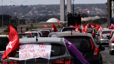 """A sign reads in Portuguese """"Copa No. Vaccine Yes, Out Bolsonaro"""" during a protest against the President's handling of the Covid-19 pandemic in Brasilia on Sunday."""