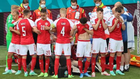 Denmark's players gather as paramedics attend to midfielder Christian Eriksen (not seen) during Saturday's match.