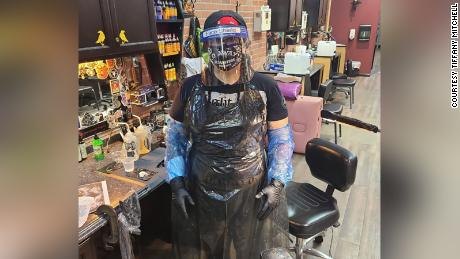 Mitchell stands in full PPE, ready for tattooing.