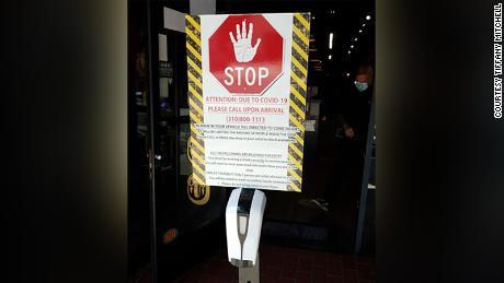 A sign hangs at Black Raven Tattoo during the pandemic with instructions for clients.