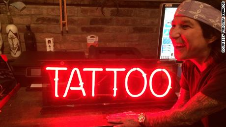 Stephanie Tamez smiles next to an old neon sign in Saved Tattoo.