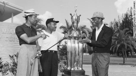 """Sifford is presented with the North-South Negro Golf Tournament trophy by night club celebrity Nat """"King"""" Cole."""