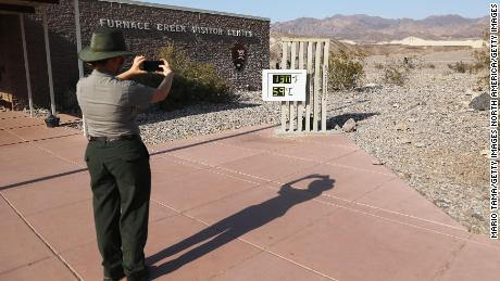 A park ranger takes a picture of an unofficial thermometer at Furnace Creek Visitor Center in California's Death Valley National Park on August 17, 2020, a day after the temperature had reached 130 degrees.