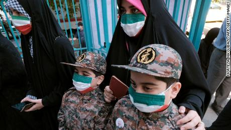 A mother and her children, wearing Islamic Revolutionary Guard Corps' uniforms, line up at a polling station on Friday.