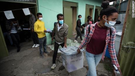 Избиратели переносят урны для голосования под дождем из распределительного центра в Аддис-Абебе, Эфиопия, 20 июня.