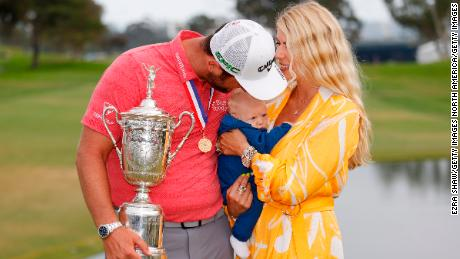 Rahm celebrates with the trophy alongside his wife, Kelley, and son, Kepa, after winning the 2021 US Open.