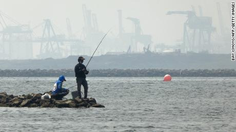 Anglers fish amid thick haze at a coastal area in Jakarta on June 20, 2020.