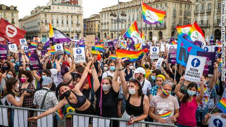 People hold placards and rainbow flags during a demonstration in support of the Zan law in Turin, Italy, on June 5.