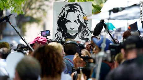 A portrait of Britney Spears looms over supporters and media members outside the court hearing concerning the singer's conservatorship at the Stanley Mosk Courthouse on Wednesday, June 23, in Los Angeles.
