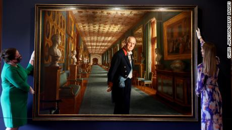 Curators adjust a portrait of Prince Philip by the artist Ralph Heimans in the Great Hall of Windsor Castle.