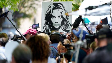 A portrait of Britney Spears looms over supporters and the media outside a court hearing concerning the pop singer's conservatorship at the Stanley Mosk Courthouse in LA, June 23.
