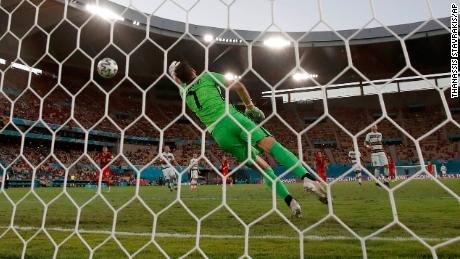 Portugal's goalkeeper Patricio fails to save the shot by Hazard.