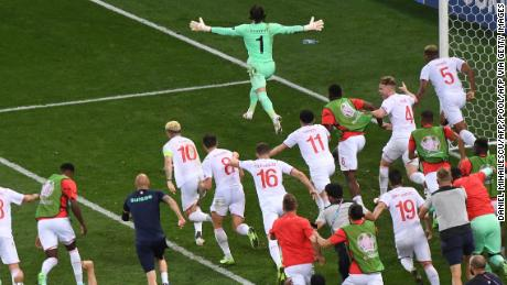 Switzerland goalkeeper Yann Sommer wheels away in celebration after saving Kylian Mbappe's penalty.