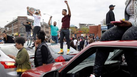 Protesters stand on cars near the intersection of in Baltimore on May 1, 2015, the day of the announcement of charges against the police officers involved in Freddie Gray's arrest.