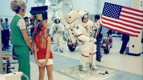 Gene Cernan deploys the U.S. Flag during training while Gene's wife, Barbara, and their daughter, Teresa (Tracy), watch. Jack Schmitt is in the background near the one-g LRV trainer. 4 August 1972. Research by J.L. Pickering  NASA