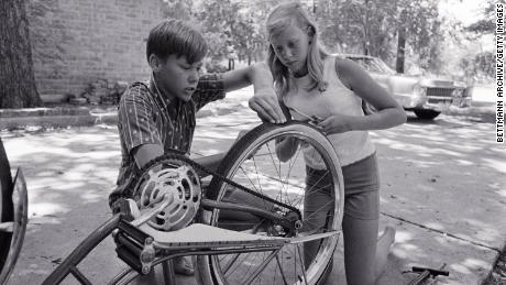 Jan Aldrin and her older brother Mike work on repairing Jan's bike tire, which she punctured with a tack. Despite their father landing on the moon, much of life back home still went on as usual.