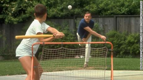 """Neil Armstrong pitches a ball to his son, Rick, at their home in March 1969. The Armstrong boys often used their backyard as a wiffle ball field, but despite this image, """"in reality (dad) wasn't in the lineup much,"""" Rick said."""