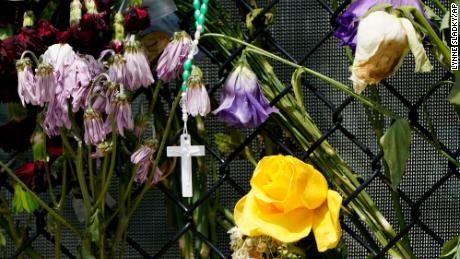 A cross hangs among wilting flowers at a makeshift memorial near the Champlain Towers South condo building.