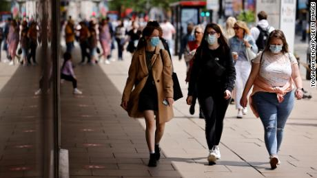 Pedestrians wear face masks while walking along Oxford Street in central London on June 6.