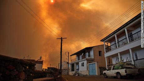 Heavy smoke covers the sky above the village of Ora in the southern slopes of the Troodos mountains, as a giant fire rages on the Mediterranean island of Cyprus, on July 3.