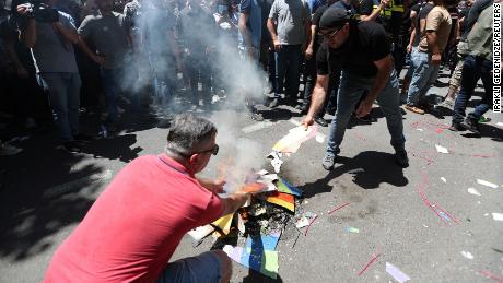 اینٹی ایل جی بی ٹی مظاہرین نے پیر کے روز مارچ سے پہلے ریلی میں حصہ لینے کے دوران اندردخش بینر جلایا۔