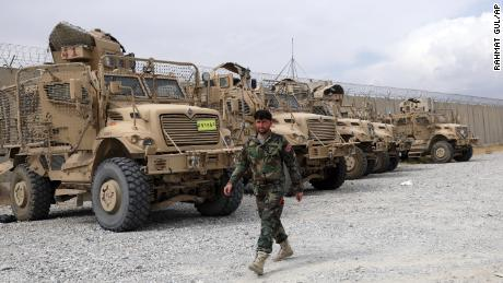 An Afghan army soldier walks past Mine Resistant Ambush Protected vehicles, MRAP, that were left after the American military left Bagram air base, in Parwan province north of Kabul, Afghanistan, Monday, July 5, 2021.