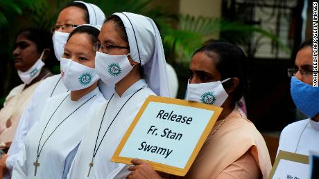 Catholic nuns hold placards during a protest against the arrest of Jesuit priest Father Stan Swamy on October 21, 2020.