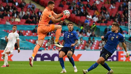 Spain goalkeeper Unai Simon makes a save whilst under pressure from Ciro Immobile.