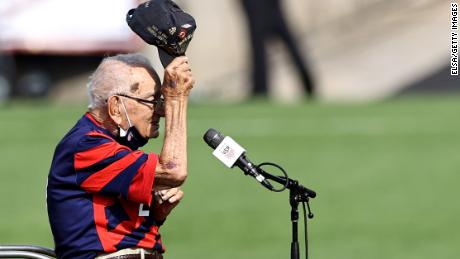 World War II veteran Pete DuPre acknowledges fans after he performed the US national anthem on a harmonica before a women's soccer match against Mexico on July 5.  (Photo by Elsa/Getty Images)