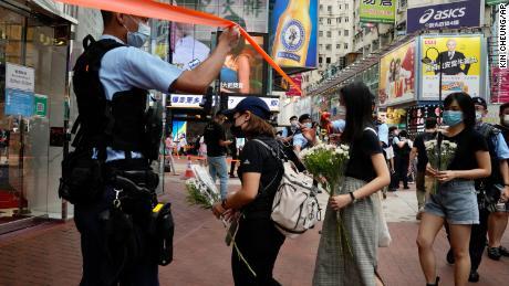 Žmonės laiko gėles, kad apraudotų užpuoliko mirtį.
