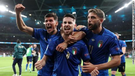 Jorginho celebrates with Matteo Pessina and Domenico Berardi after scoring Italy's winning penalty.