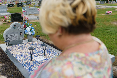 Pamela Dinkins looks at the grave of her son Eric, who was shot and killed in 2015.