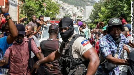 Žmonės džiūgauja, kai policijos automobilis važiuoja pro policijos nuovadą, kur liepos 8-ąją Port Prensas mieste buvo laikomi ginkluoti vyrai, apkaltinti dalyvavimu prezidento Jovenelio Moise'o nužudyme.