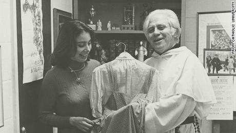 An archive photo of Rev. Gilbert Hartke holding the dress.