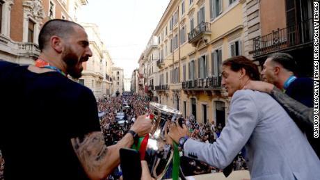 Leonardo Bonucci and Roberto Mancini celebrate during national team's open-top bus parade in Rome.